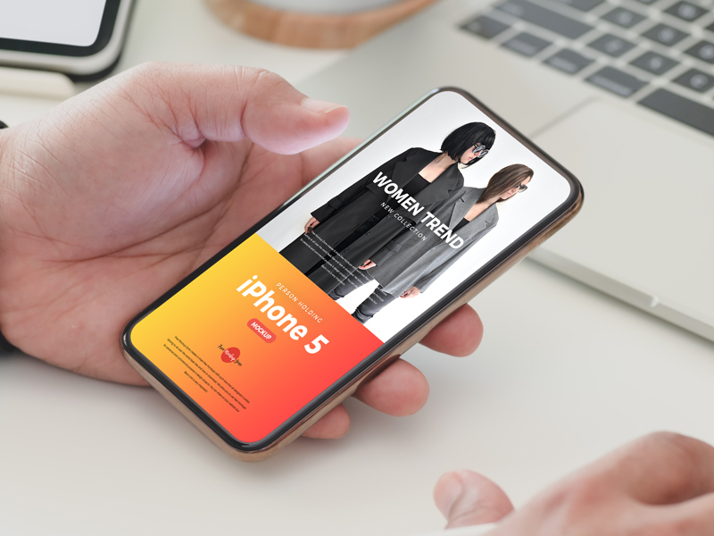 Free-Person-Holding-iPhone-5-Mockup-PSD