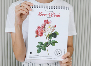 Free-Person-Showing-Sketch-Book-Mockup-300.jpg
